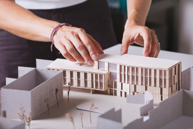 A person putting together a building model