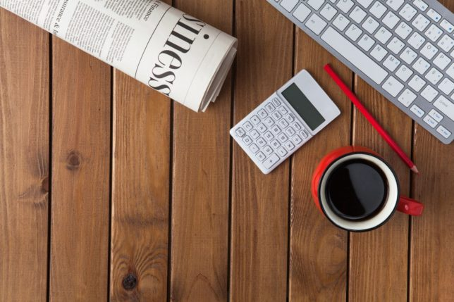 Keyboard, calculator, red colored pencil, cup of coffee in red mug, and newspaper on a desk