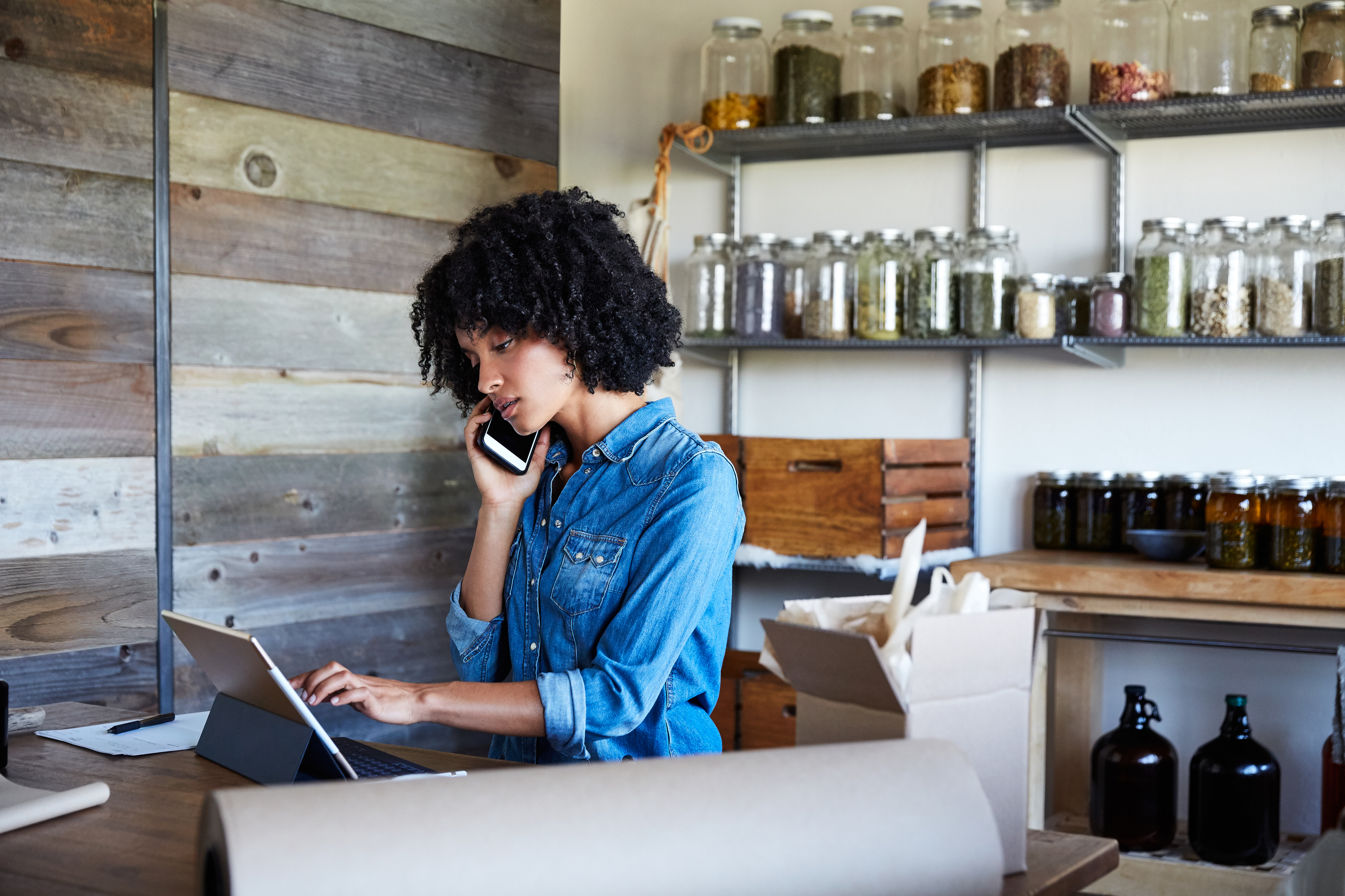A business woman in a jean shirt talking on her cell phone and touching a tablet device