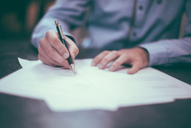 Person holding a black pen signing a stack of papers