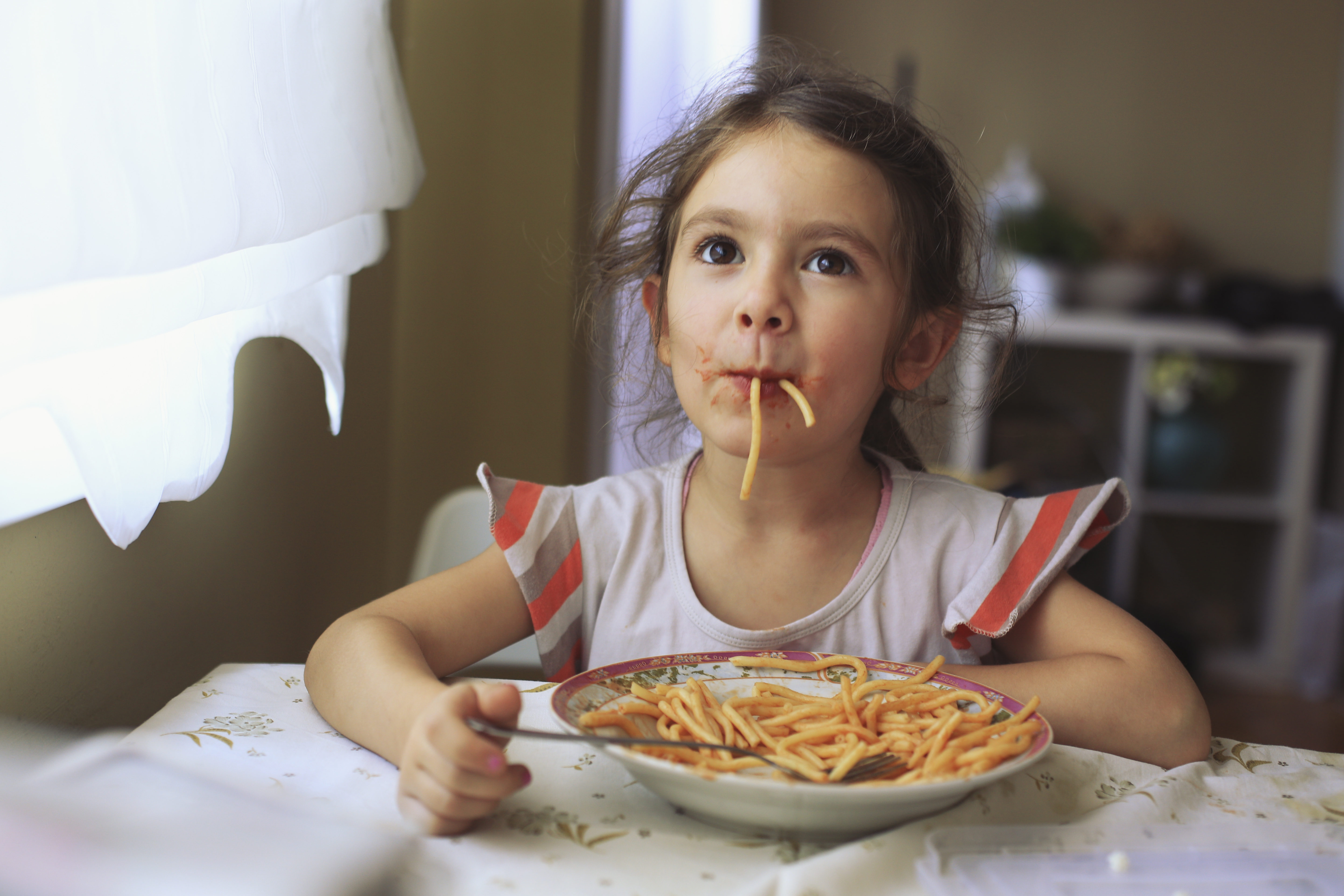 Little girl sitting at home and eating plate full with spaghetti
