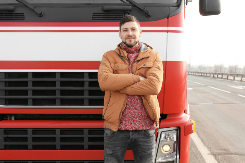 White male in a brown coat standing in front of a large red and white van.