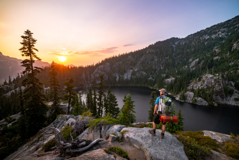 White male carrying a backpack standing on top of a cliff watching the sunrise