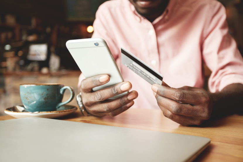 African American man sitting at a table holding a debit card while looking at his cell phone.