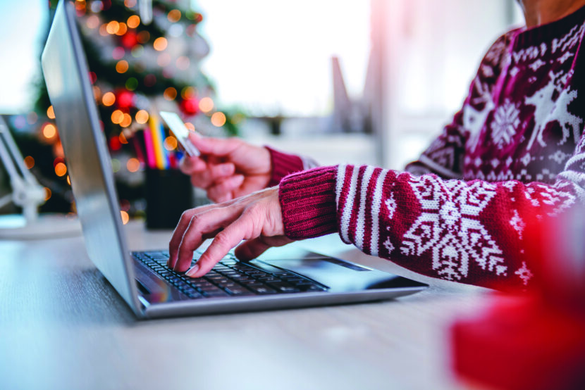 Person in red holiday sweater sitting at table purchasing something on laptop with their credit card