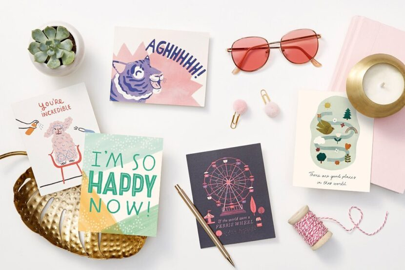 Aerial view of five cards from Compendium, pink sunglasses, a candle, paperclips, pen and succulent plant.