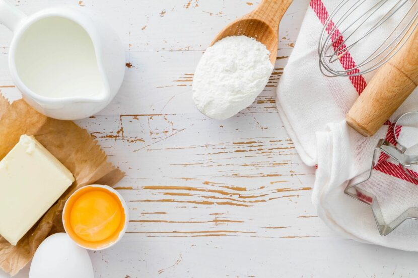 Aerial view of wooden spoon full of flour, a wire whisk, white and red dish towel and container of milk