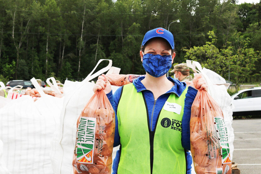 Female volunteer at Emergency Food Network wearing blue mask and green vest holding up two bags of potatoes