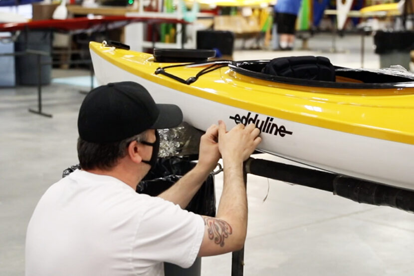 Male putting Eddyline sticker on side of kayak in warehouse